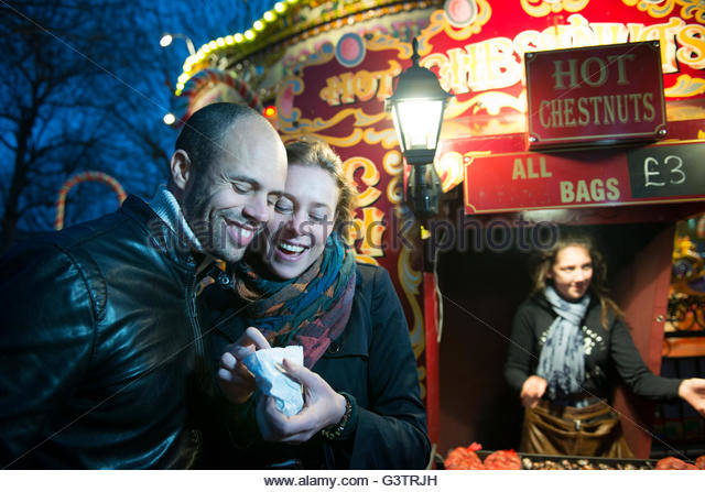 a-couple-standing-in-front-of-a-vendor-selling-hot-chestnuts-on-the-g3trjh